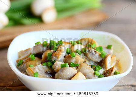 Mushrooms slices in a sour cream sauce. Mushrooms stewed with sour cream and green onions in a bowl. Healthy vegetarian snack recipe. Vintage wooden table. Closeup