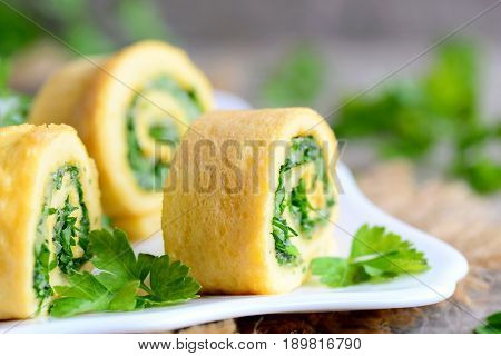 Cheese and parsley stuffed omelette. Cut stuffed omelette with cheese and parsley. Delicious and healthy rolls idea. Eating eggs for breakfast. Rustic style. Closeup