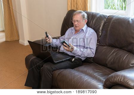 Elderly Man Looking Confused By Mobile Phones With A Laptop On His Knee