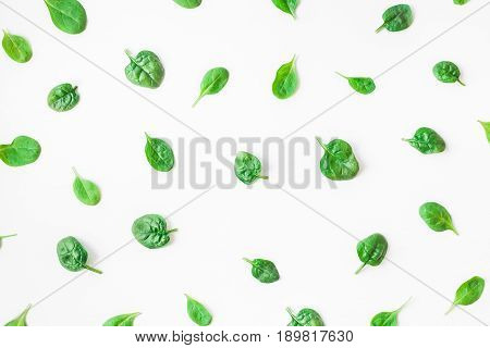 Spinach leaves on white background. Pattern made of spinach. Flat lay top view
