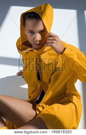 Seductive African American Woman Wearing Raincoat And Hood Posing In Studio