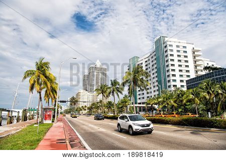 Miami USA - January 10 2016: cars driving on city road along sea coast with modern buildings green palms and paved promenade on cloudy sky background. Travelling. Summer vacation Colins drive