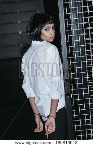 Woman In White Shirt With Cuffs On Hands Standing Near Grate