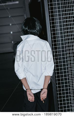 Back View Of Woman In White Shirt With Cuffs On Hands Standing Near Grate