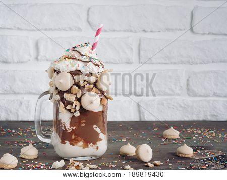 Close up view of freakshake in mason jar on brown table. Freaked milkshake with chocolate, biscuit cookies and sugar sprinkling. Copy space. Trendy food concept
