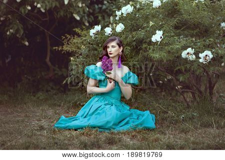 Woman sits on the grass holding a lilac branch in her hands she dreams.