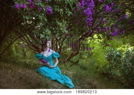 Lovely woman under a lilac bush sitting on the grass she dreams.