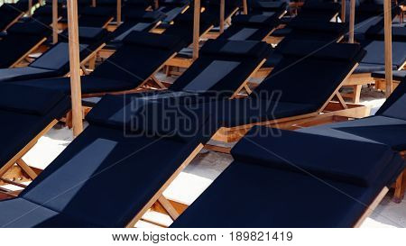 Rows of sunbeds under beach umbrellas at poolside on luxury tropical beach resort. Loungers with nobody. Recreational activity equipment hotel leisure facilities concept. Summer holidays background.