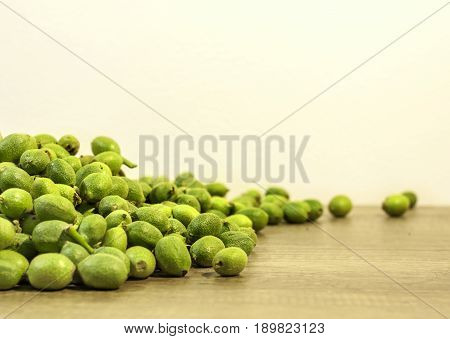 A lot green young walnuts in husks on brown wooden kitchen table and white background