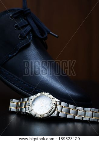 Stylish male shoe with watch over dark