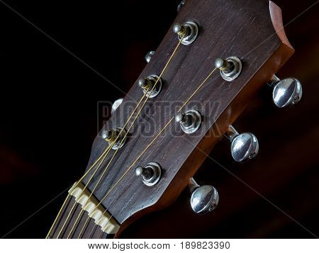 detail of Tuning head for acoustic guitar peg close up shot black background