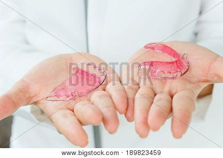 Dentist holding Retainer, Orthodontics Dental concept background