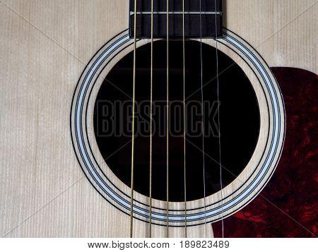 Close up shot of acoustic guitar. Strings sound hole bridge pickguard