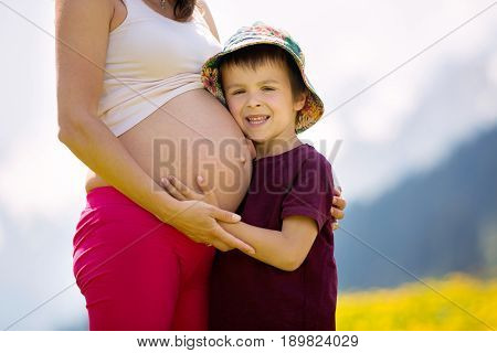 Young Pregnant Woman And Her Child In A Dandelion Field In Alps