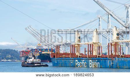Oakland CA - June 01 2017: Tugs move vessels that should not move themselves such as ships in a crowded harbor. PATRIOT assists MOUNT HIKURANGI to maneuver out of the Port of Oakland.