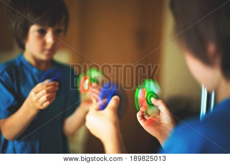 Little Child, Boy, Playing With Green And Blue Luminous Fidget Spinner Toy To Relieve Stress