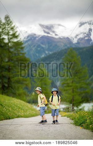 Two Children, Boy Brothers, Walking On A Little Path In Swiss Alps