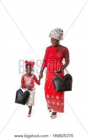 Beautiful African woman and little girl in traditional red clothing with black wicker tote bag. Isolated on the white studio background