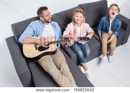 High Angle View Of Smiling Father Playing Guitar And Cute Happy Children Sitting On Sofa
