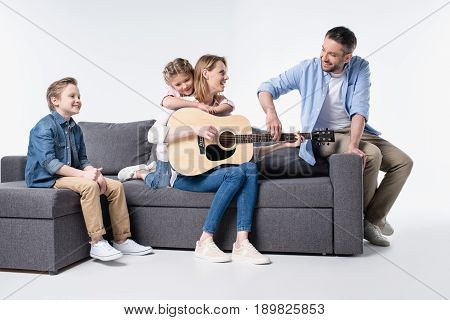 Happy Young Family With Two Children Sitting Together On Couch And Playing Guitar