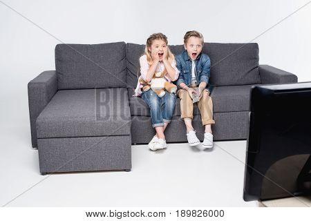 Scared Boy And Girl Sitting On Sofa And Watching Tv Together