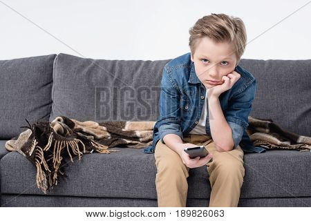 Pre-adolescent Bored Kid Boy Sitting On Sofa And Using Remote Control