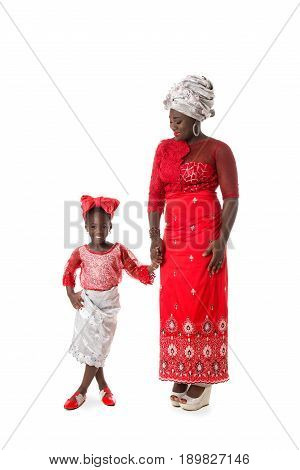 Beautiful African woman with little girl in traditional red colored clothing . Isolated on the white studio background
