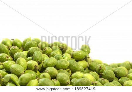 A lot green young walnuts in husks on white background