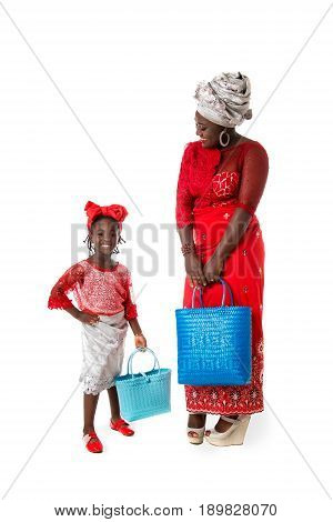 Beautiful African woman with little girl in traditional clothing with bright wicker tote bag. Isolated on the white studio background