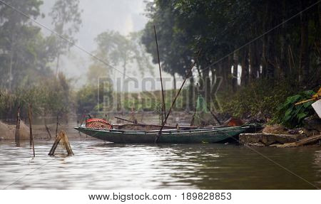 Traditional boats and luxuriant tropical vegetation on the river in Tam Coc,Vietnam. Vietnam travel landscape and destinations background.