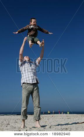 Jungen spielen mit Vater. Vater seinen Sohn in die Luft zu werfen.