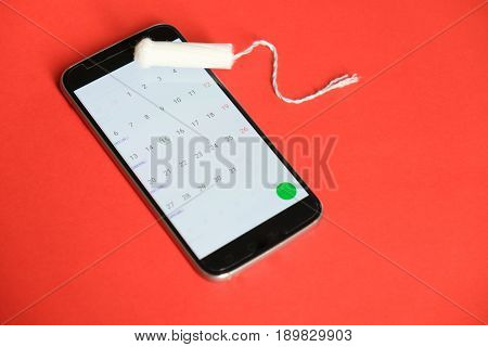Menstrual Tampon And Smart-phone On Red Background