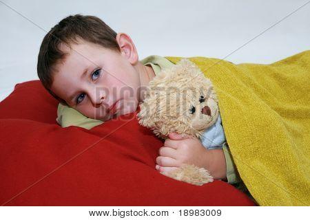 Junge im Bett. Fünf Jahre junge mit Teddybär im Bett liegend.