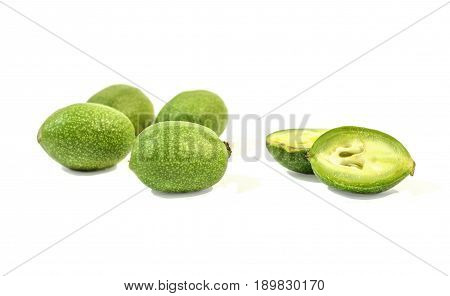 Green Walnuts, with one walnut cut Isolated on White Background