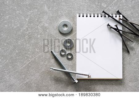 Construction tools. The screws and bolts arranged around blank spiral bound note book paper on concrete background. Repair, home improvement concept. Free space for text, top view, flat lay