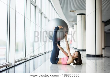 Woman Working Out With Exercise Ball In Gym. Pilates Woman Doing Exercises In The Gym Workout Room W