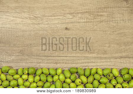 Green young walnuts in husks on the bottom in row on wooden table