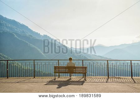 The man on the bench admires a beautiful view of the green mountains. Rosa Khutor Sochi Mountain Olympic Village