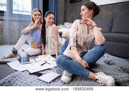 Smiling Businesswoman Looking At Grimace Colleagues During Work Process