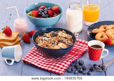 Breakfast with wholegrain cereals on wooden table.
