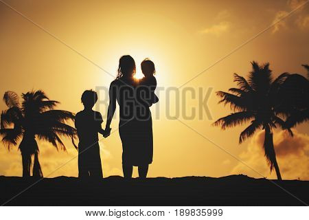 mother with little son and daugther walking at sunset beach