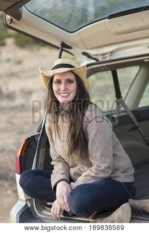 Caucasian woman smiling in hatchback of car