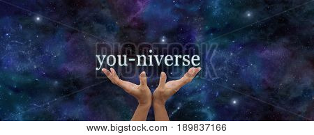 YOU are EVERYTHING - Hands reaching up with the word YOU-NIVERSE floating above against dark blue night sky background with plenty of copy space