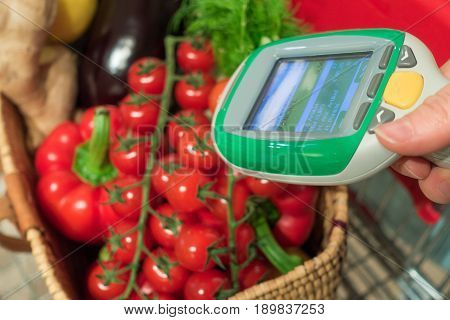 Woman customer using handheld scanner device in supermarket. Automatic object recognition of vegetables. The future of grocery shopping.