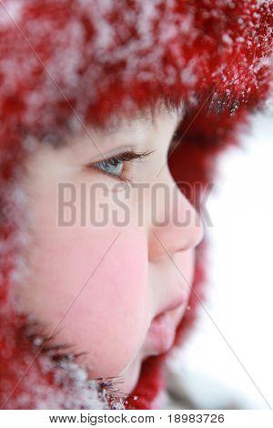 Winter Baby. Ein Jahr altes Baby in warme Kleidung gekleidet. Baby mit Schneeflocken auf seine Kappe.