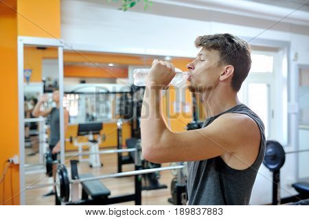 Young athlete drinks a cool drink in the gym after the training