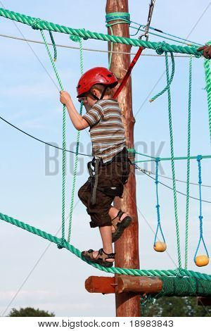 Portrait of 5 years old boy wearing helmet and climbing. Child in a wooden abstacle course in adventure playground
