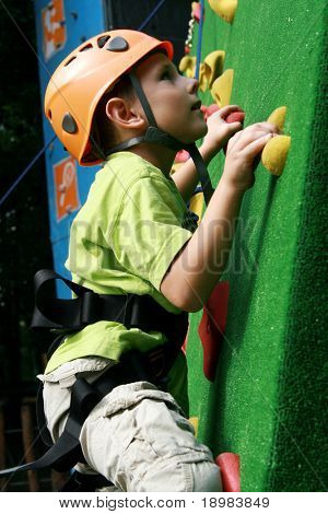 5 years old child climbing on a wall in an outdoor climbing center