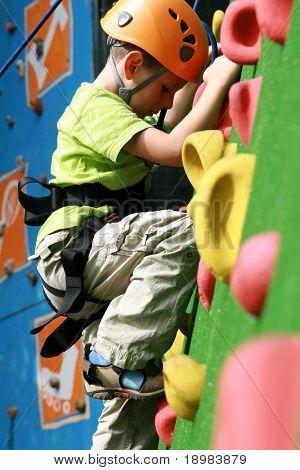 child climbing on a wall in an outdoor climbing center