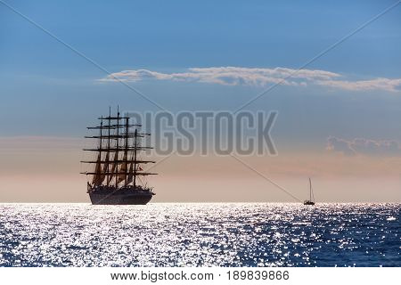The world's largest sailing ship with five masts leaves at sunset in the open sea. poster
